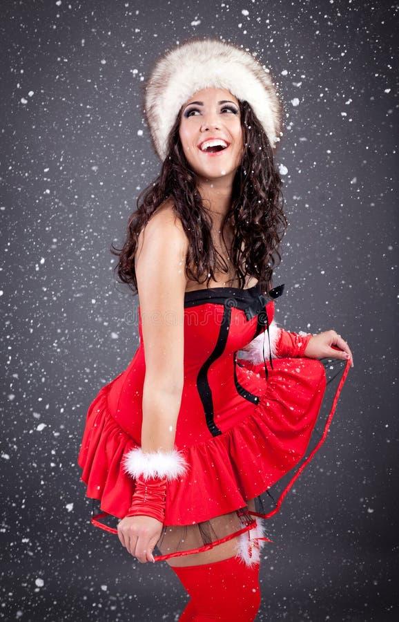 Muchacha atractiva de santa en vestido rojo sobre fondo nevoso de la Navidad foto de archivo