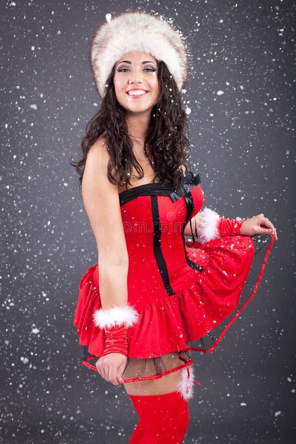 Muchacha atractiva de santa en vestido rojo sobre fondo nevoso de la Navidad fotos de archivo