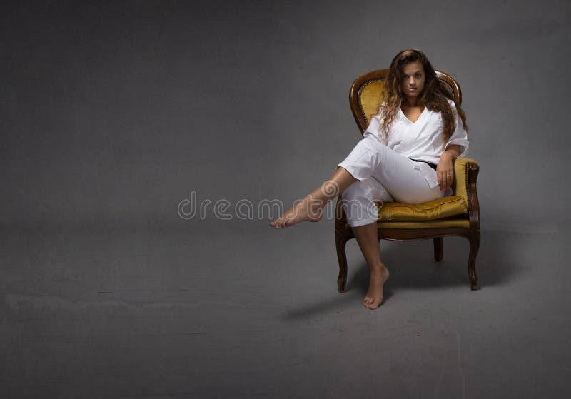 Muchacha atractiva del karate que se sienta en el sofá foto de archivo libre de regalías