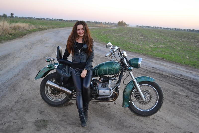 Muchacha atractiva del motorista que se sienta en la motocicleta de encargo del vintage La forma de vida al aire libre entonó el  imagen de archivo libre de regalías