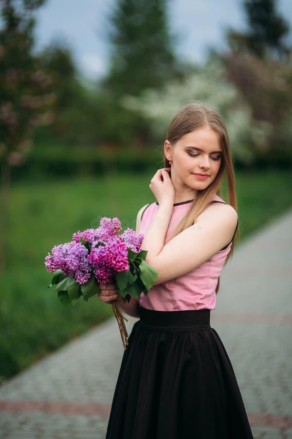 Muchacha atractiva del pelo rubio sostener un ramo de lila en manos Muchacha encantadora afuera foto de archivo
