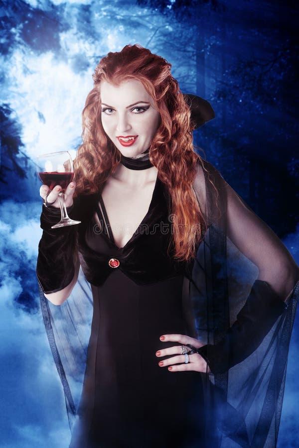 Muchacha atractiva del vampiro con el vidrio de sangre en las maderas en la noche imagenes de archivo
