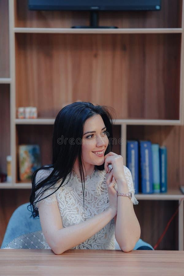 Muchacha atractiva emocional joven que se sienta en un escritorio en una oficina o un auditorio moderna fotografía de archivo libre de regalías
