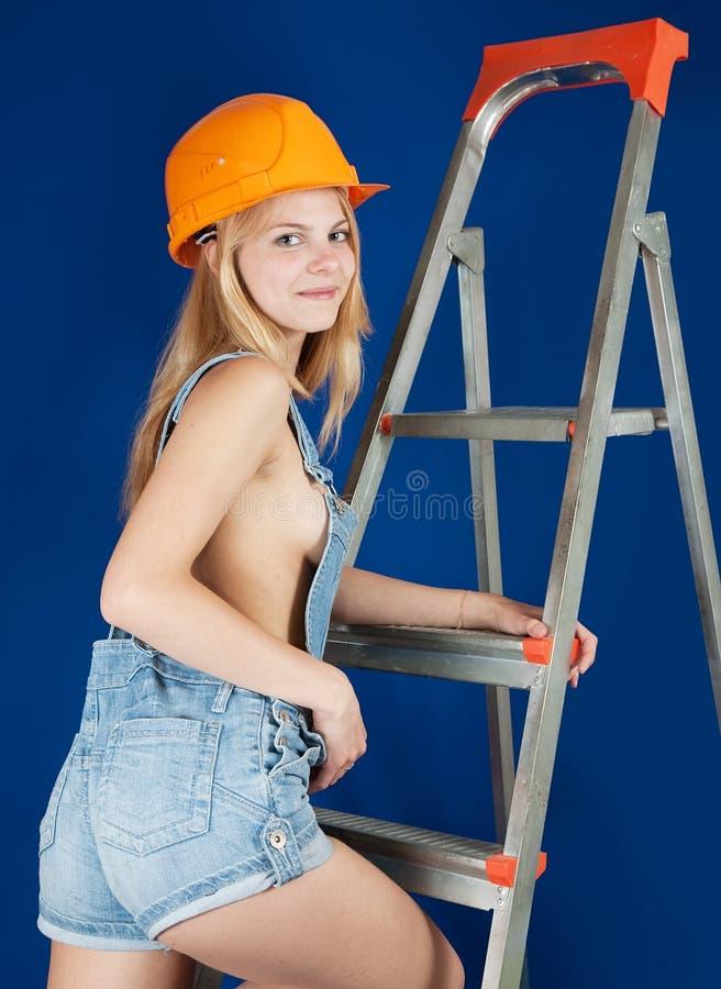 Muchacha atractiva en el stepladder sobre azul fotografía de archivo libre de regalías