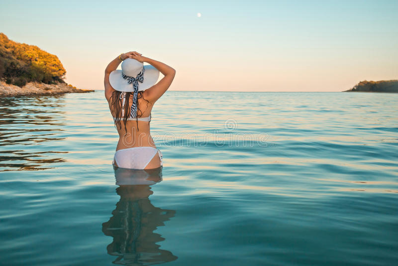 Muchacha atractiva en el traje de baño blanco con el sombrero que mira el mar el crepúsculo con la Luna Llena y la isla en fondo imágenes de archivo libres de regalías