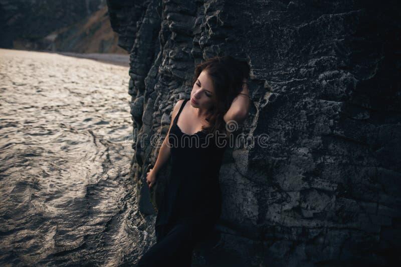 Muchacha atractiva en el vestido negro que se coloca que se inclina contra la roca imagen de archivo