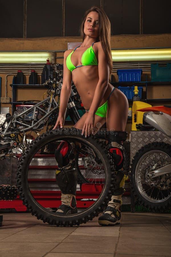 Muchacha atractiva en garaje con los neumáticos de la bici fotografía de archivo