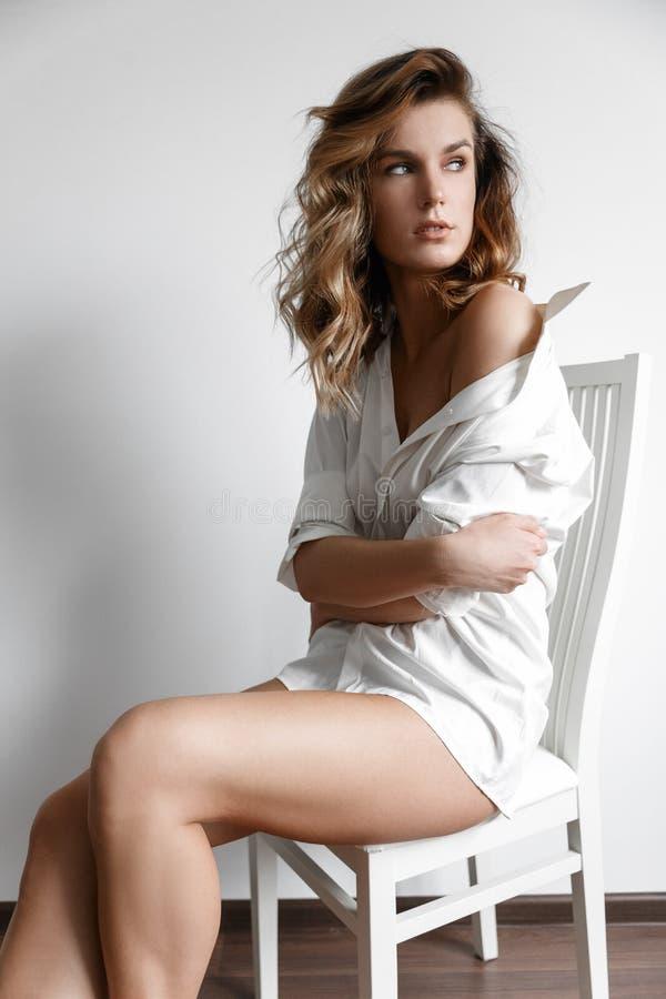 Muchacha atractiva en la camisa blanca en una silla blanca fotos de archivo