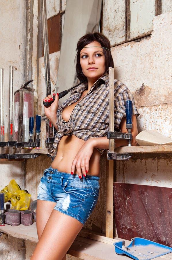 Muchacha atractiva en los carpinteros del departamento de la carpintería imágenes de archivo libres de regalías