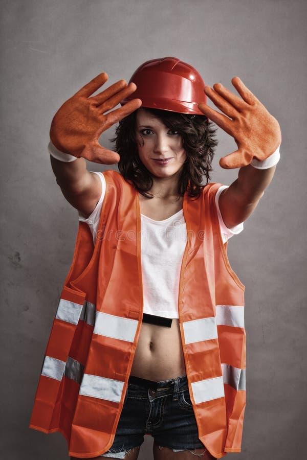Muchacha atractiva en muestra de la parada de la demostración del casco de seguridad imagenes de archivo