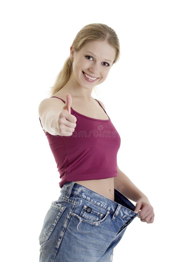 Muchacha atractiva en peso perdido de los pantalones vaqueros foto de archivo