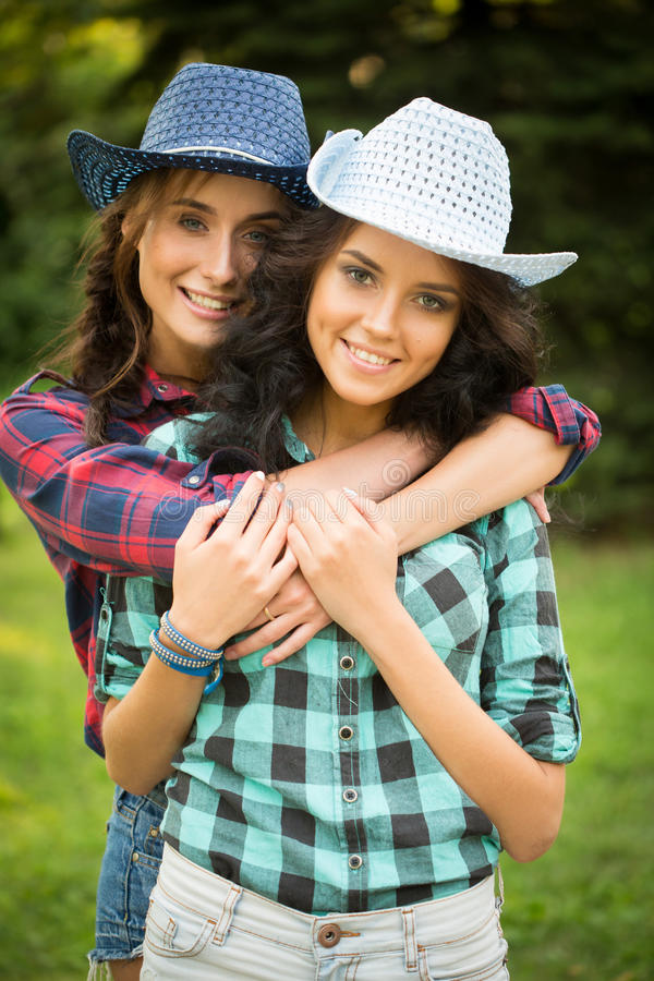 Muchacha atractiva en sombreros de vaquero y camisas de tela escocesa fotos de archivo libres de regalías