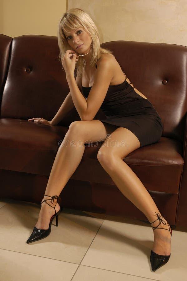 Muchacha atractiva en un sofá fotos de archivo