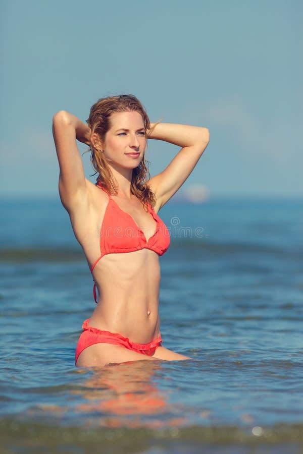 Muchacha atractiva en un traje de baño en el mar fotografía de archivo