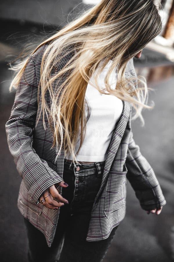 Muchacha atractiva en una chaqueta y una camiseta blanca que camina a lo largo de la calle imagen de archivo libre de regalías