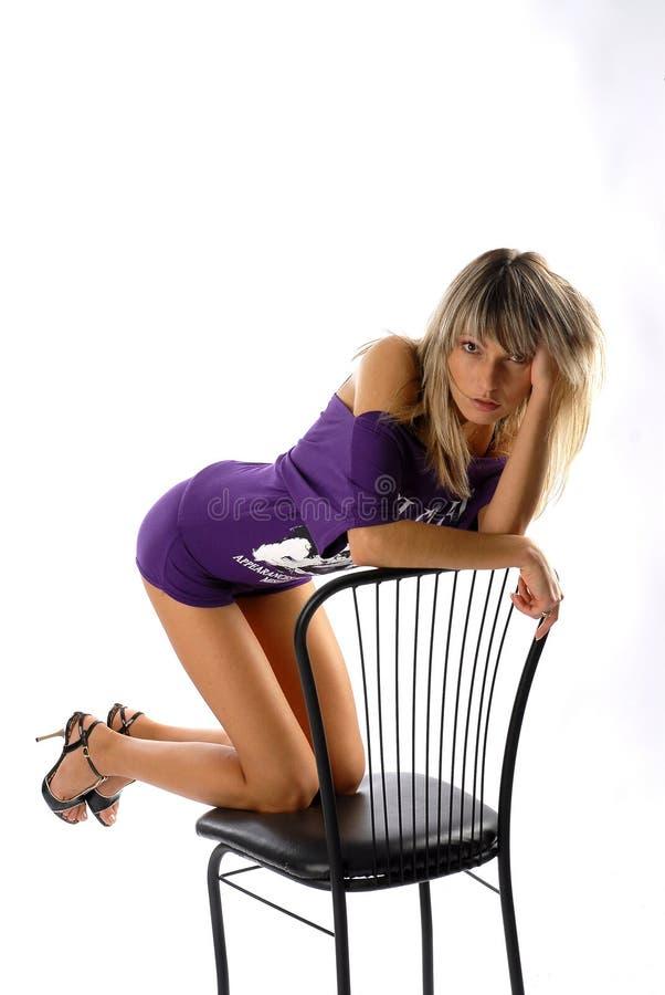 Muchacha atractiva en una silla negra fotos de archivo