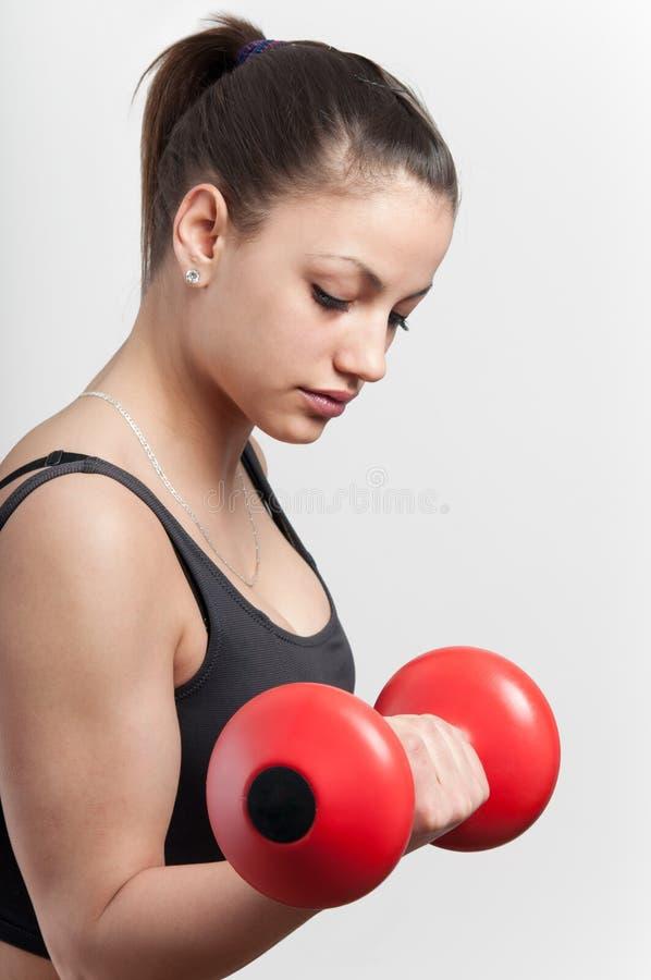 Muchacha atractiva fuerte con pesa de gimnasia fotografía de archivo