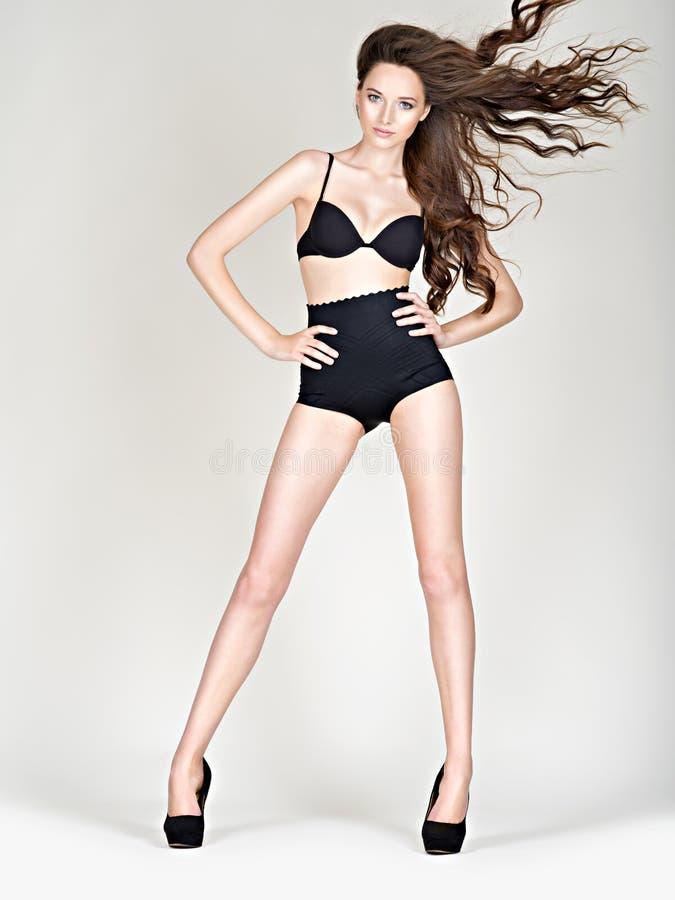 Muchacha atractiva hermosa con el pelo largo que lleva la ropa interior negra fotografía de archivo libre de regalías