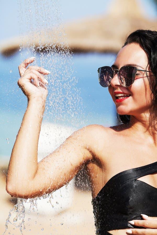 Muchacha atractiva hermosa con la piel sana en bikini rayado elegante, imagenes de archivo