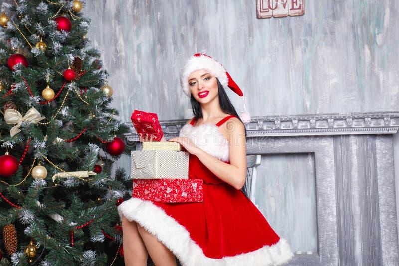 Muchacha atractiva hermosa que desgasta la ropa de Papá Noel Mujer sonriente con el regalo grande y pequeño Mujeres en el vestido fotografía de archivo libre de regalías