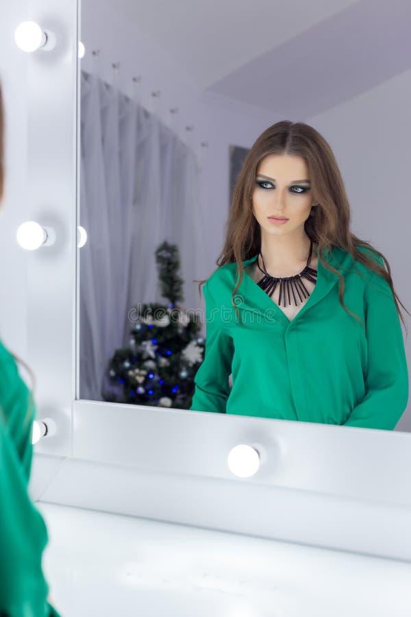 Muchacha atractiva hermosa que se coloca en el espejo con un maquillaje festivo brillante en colores verdes en un vestido de noch imagenes de archivo