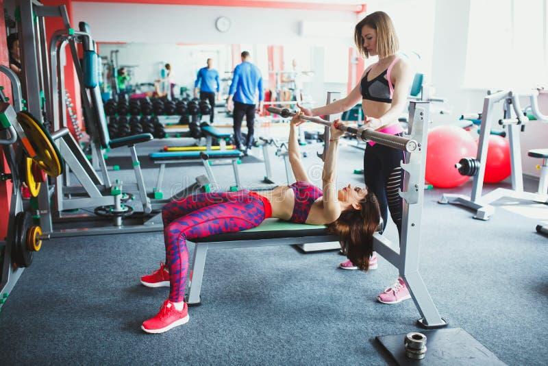 Muchacha atractiva joven con el instructor personal en el gimnasio imagen de archivo libre de regalías