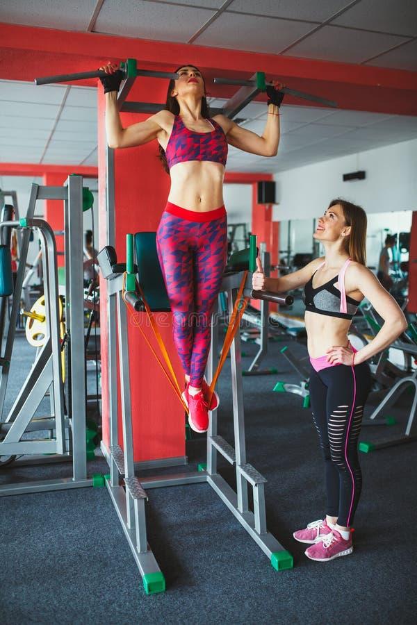 Muchacha atractiva joven con el instructor personal en el gimnasio fotografía de archivo libre de regalías