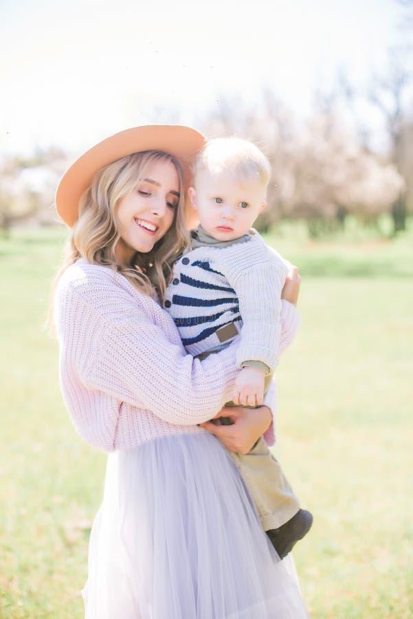 Muchacha atractiva joven con el pelo rubio con un pequeño niño pequeño en primavera en un jardín enorme fotografía de archivo libre de regalías