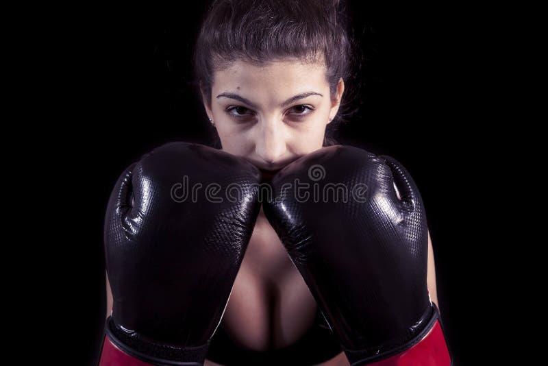 Muchacha atractiva joven con los guantes de boxeo en fondo negro fotografía de archivo