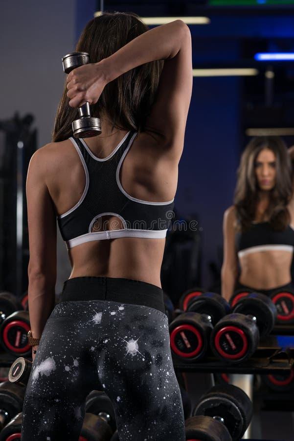 Muchacha atractiva joven de la aptitud en el gimnasio que hace ejercicios foto de archivo libre de regalías