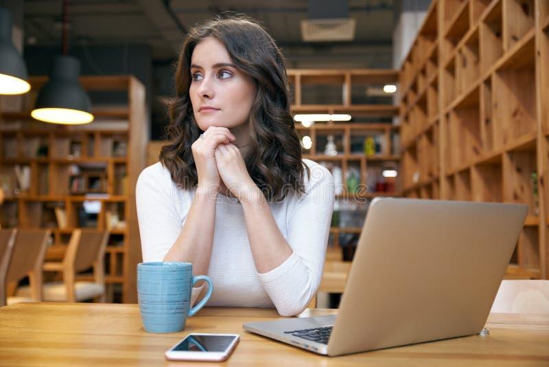 Muchacha atractiva joven de la mujer elegante en la ropa casual que se sienta en una tabla en un café con un ordenador portátil foto de archivo