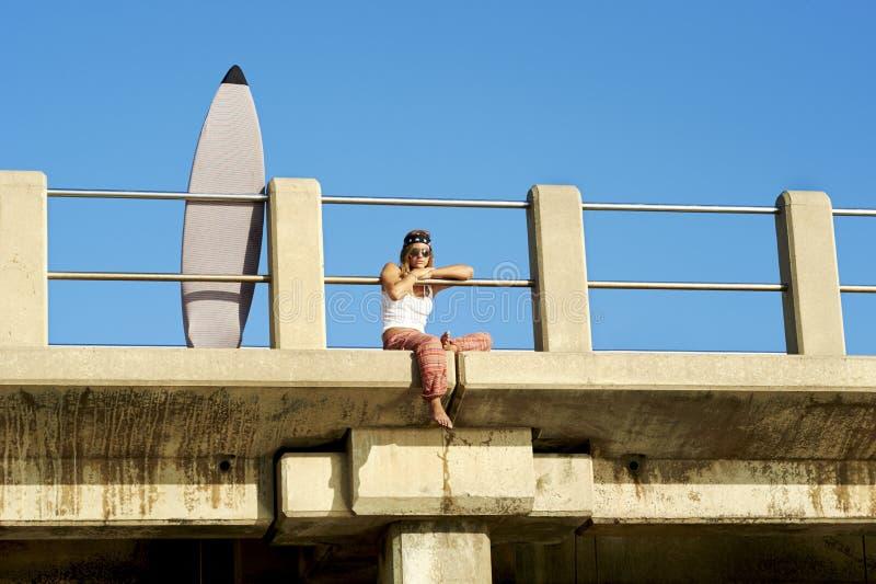 Muchacha atractiva joven de la persona que practica surf que se sienta en el embarcadero con la tabla hawaiana fotografía de archivo