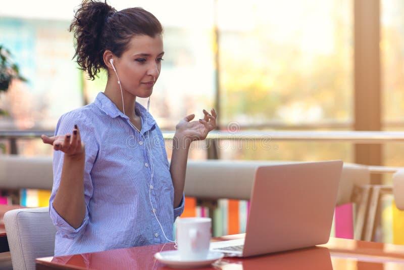 Muchacha atractiva joven de la raza mixta que está sonriendo mirando su pantalla del ordenador portátil durante la llamada video foto de archivo libre de regalías
