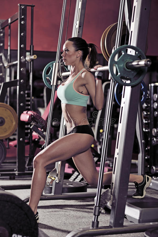 Muchacha atractiva joven en el gimnasio que hace posición en cuclillas en fondo rojo fotos de archivo libres de regalías