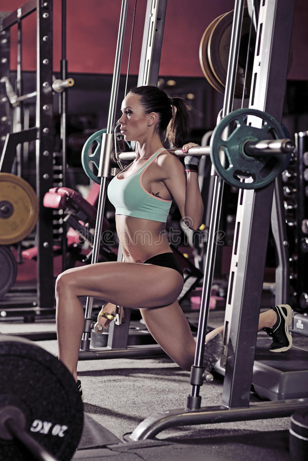 Muchacha atractiva joven en el gimnasio que hace posición en cuclillas en fondo rojo fotografía de archivo