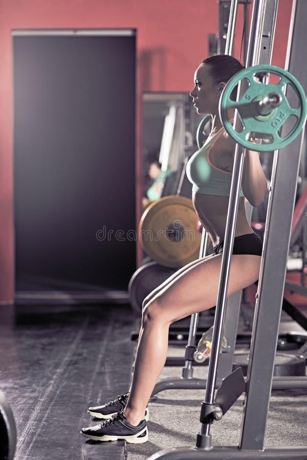 Muchacha atractiva joven en el gimnasio que hace posición en cuclillas en fondo rojo foto de archivo