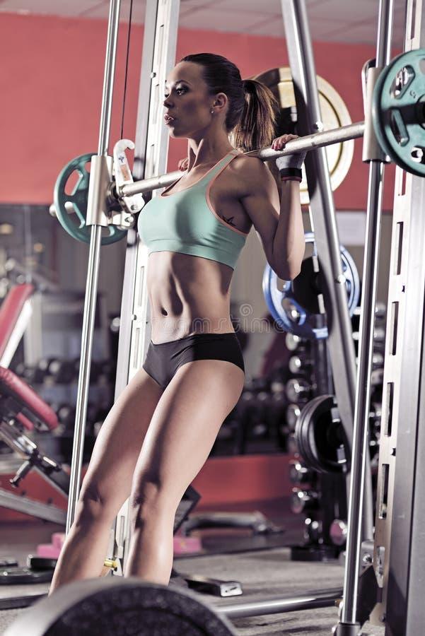 Muchacha atractiva joven en el gimnasio que hace posición en cuclillas en fondo rojo fotos de archivo