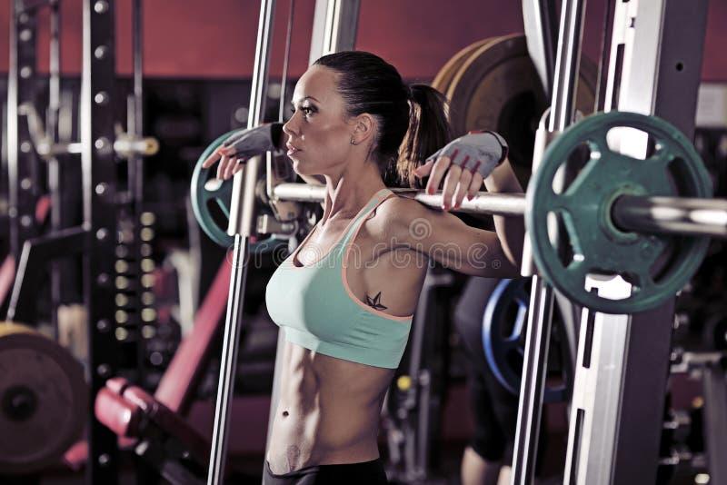 Muchacha atractiva joven en el gimnasio que hace posición en cuclillas en fondo rojo fotografía de archivo libre de regalías