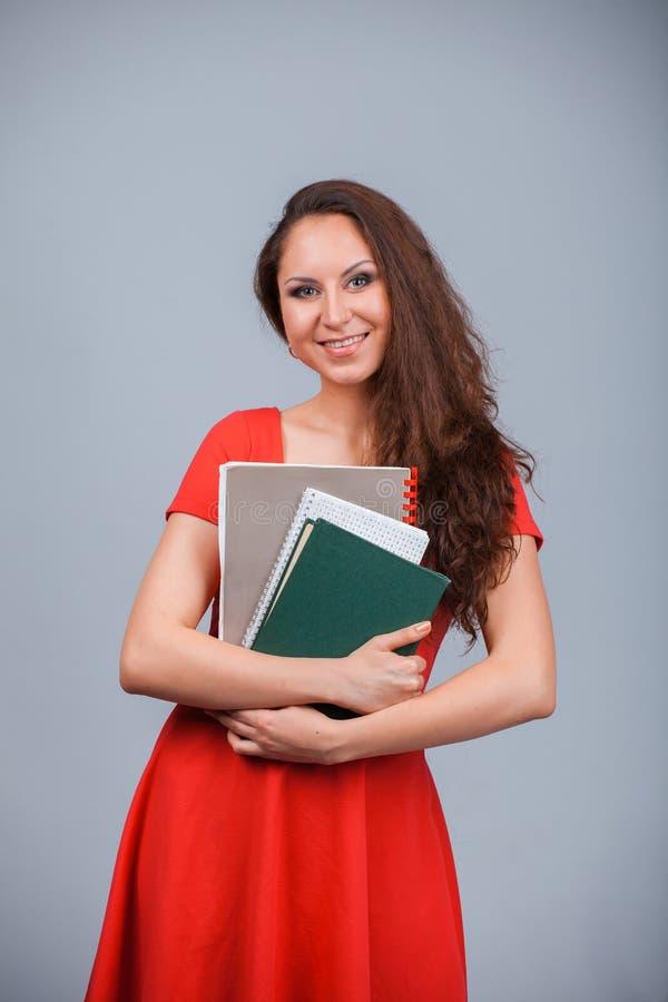 Muchacha atractiva joven en rojo con las carpetas imagen de archivo libre de regalías