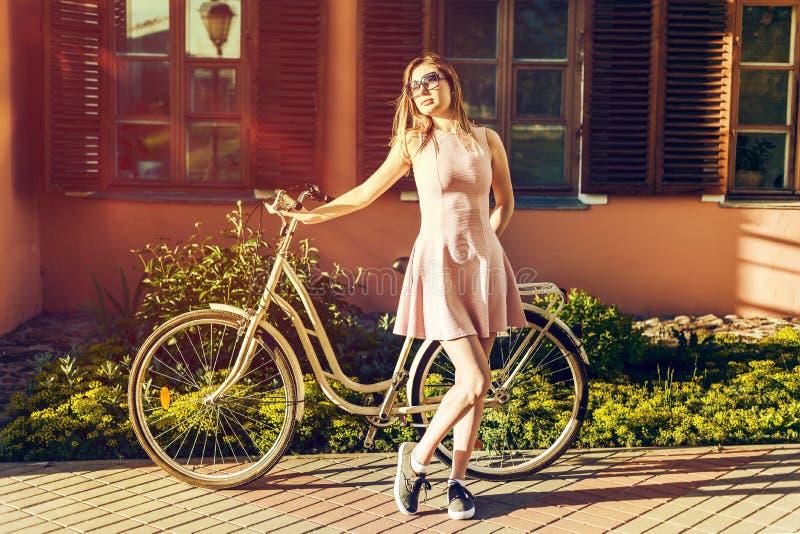 Muchacha atractiva joven en una bicicleta en retrato de presentación integral en vestido rosado la satisfacen con el sol imagen de archivo libre de regalías