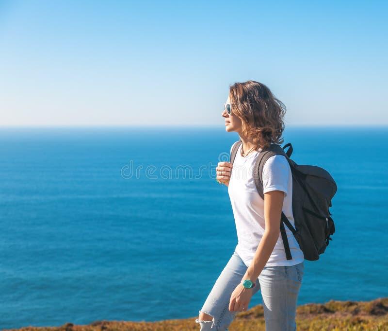 Muchacha atractiva joven en una camiseta blanca y vaqueros que camina en a foto de archivo libre de regalías