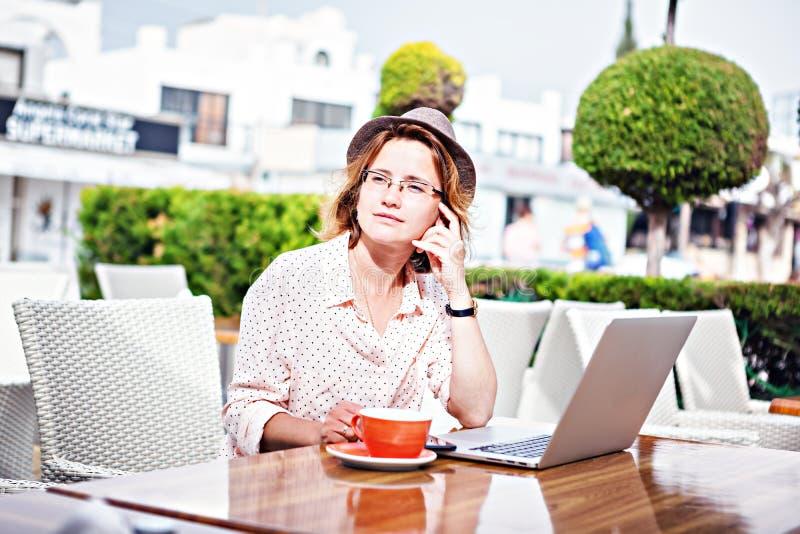 Muchacha atractiva joven en vidrios con un ordenador portátil y una taza de coff imagenes de archivo