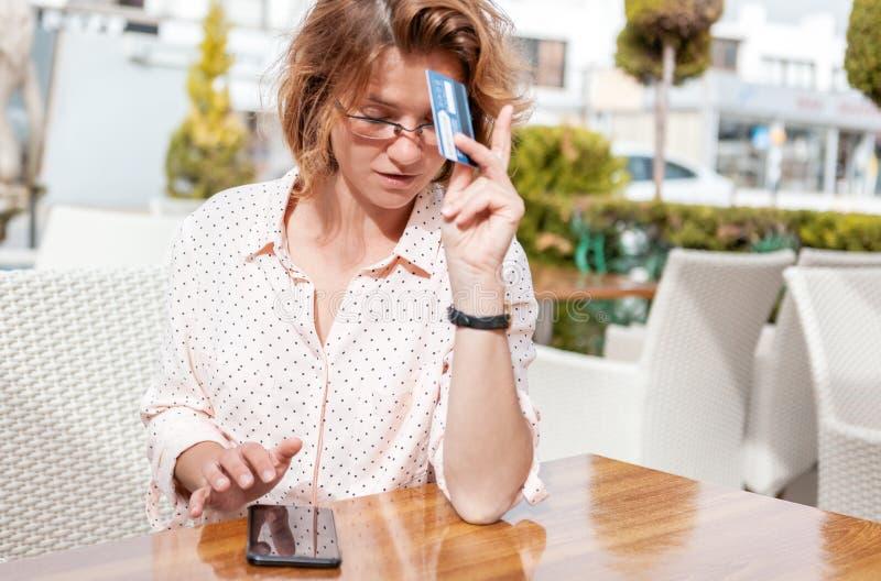Muchacha atractiva joven en vidrios con una tarjeta de crédito y un teléfono fotos de archivo
