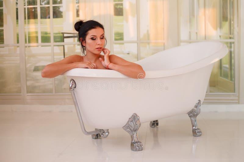 Muchacha atractiva joven hermosa con el pelo oscuro en bañera fotografía de archivo