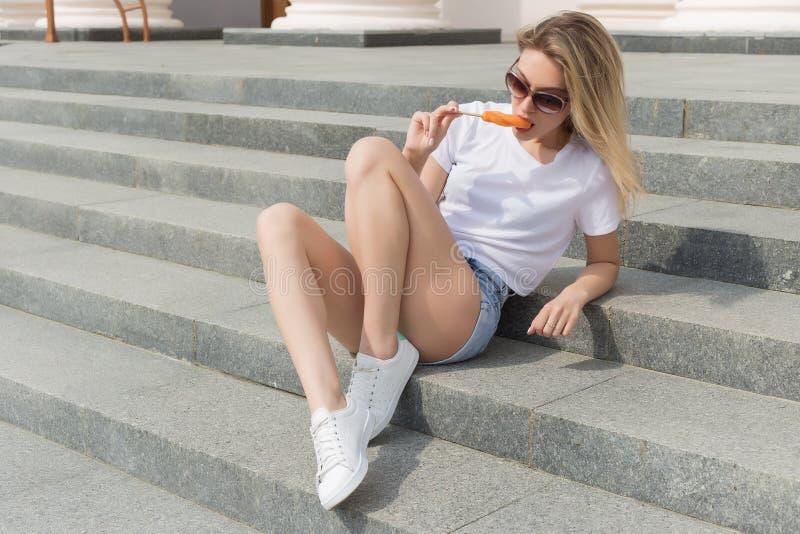 Muchacha atractiva joven hermosa en gafas de sol que come el helado en la escalera y que lame los labios regordetes al día calien foto de archivo