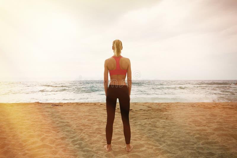 Muchacha atractiva joven que hace entrenamiento del deporte la playa vacía de la arena Mujer de la aptitud que gasta el mar al ai imagenes de archivo