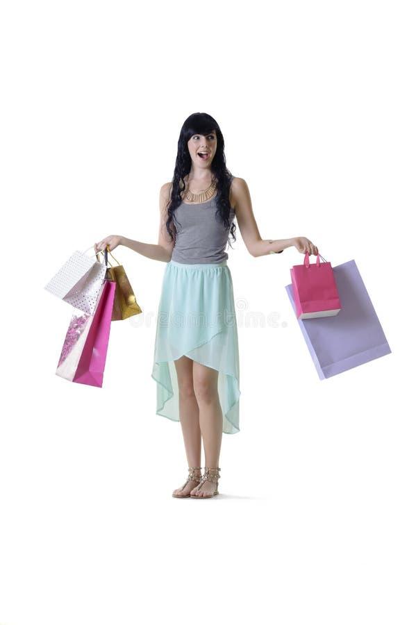 Muchacha atractiva joven que mira sorprendida los paquetes de las compras de la venta que llevan fotos de archivo