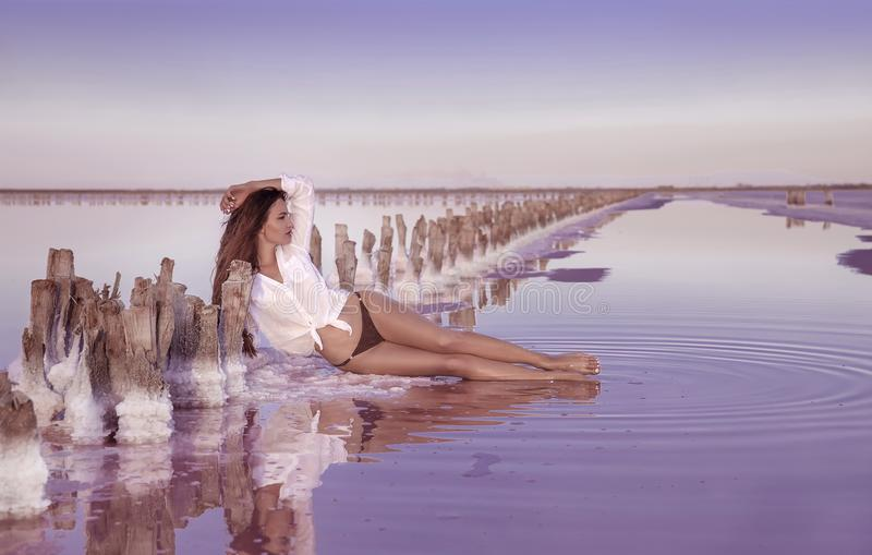 Muchacha atractiva libre hermosa en el traje de baño blanco que presenta en la playa salada fotos de archivo