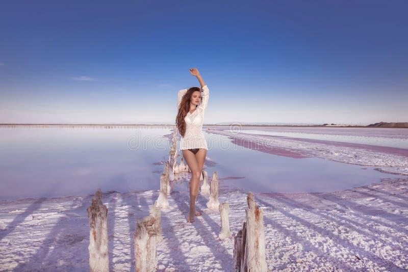 Muchacha atractiva libre hermosa en el traje de baño blanco que presenta en la playa salada fotografía de archivo