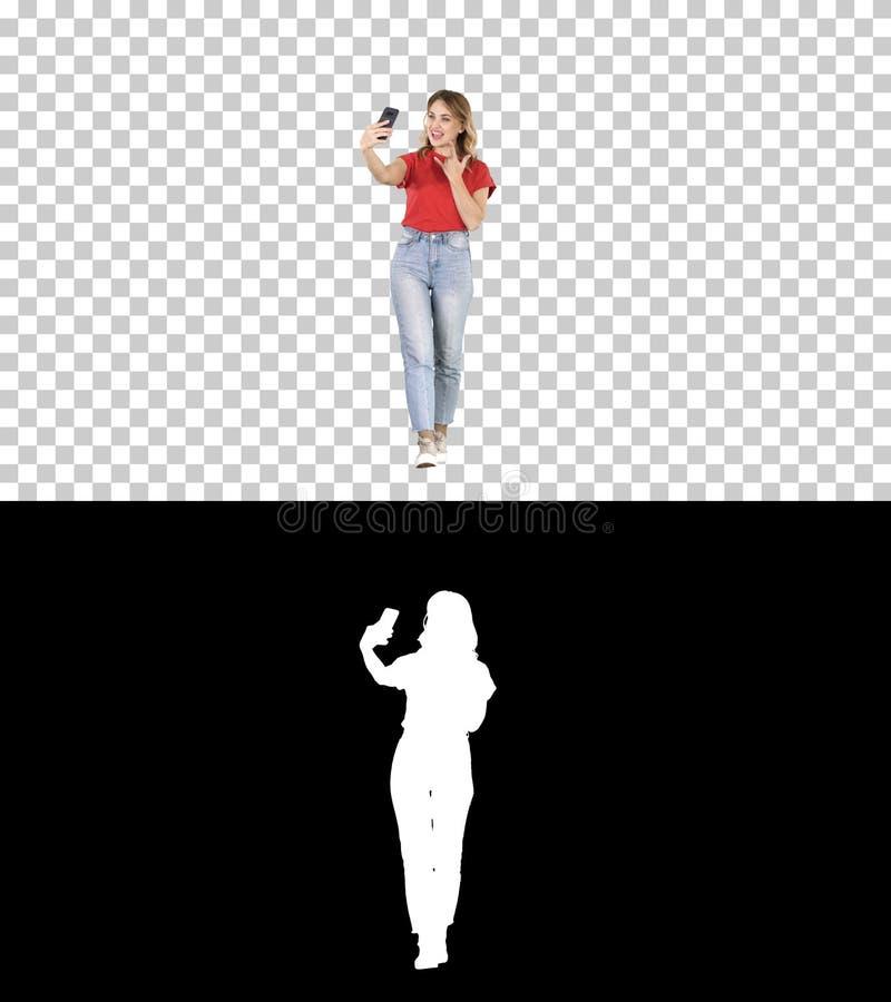 Muchacha atractiva linda con el pelo rizado rubio que camina y que hace el selfie, Alpha Channel foto de archivo